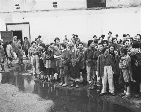 Female survivors gather outside a barracks in the newly