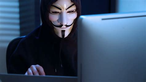 The hacker in a mask of Guy Fawkes uses the computer late