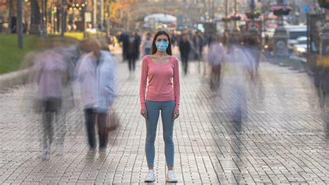 The girl with face mask stands in the crowded street